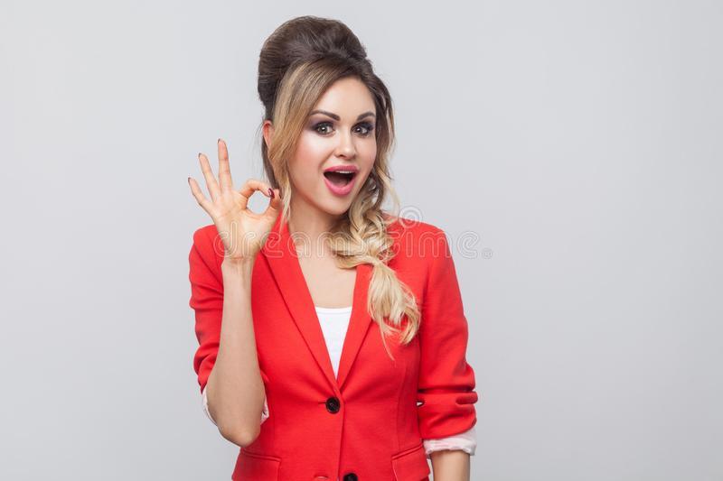 Portrait of amazed beautiful business lady with hairstyle and makeup in red fancy blazer, standing with Ok sign and looking at. Camera. indoor studio shot royalty free stock photo
