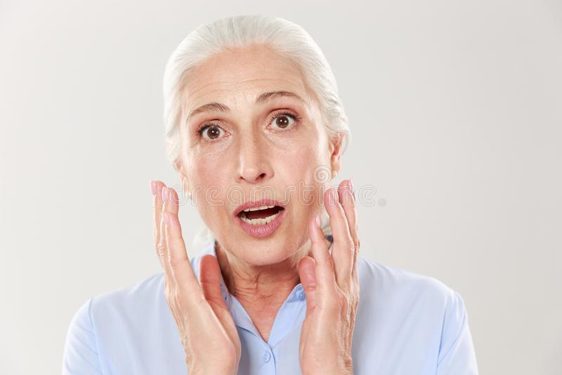 Portrait of amazed beautiful old woman, looking at camera. Isolated on white background royalty free stock photos