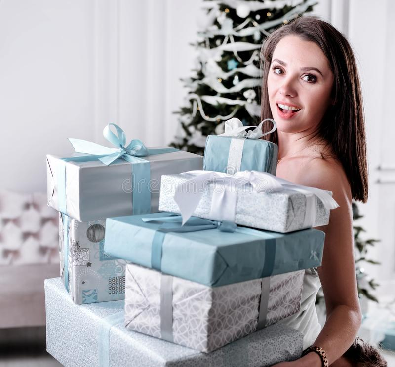 Portrait of an amazed, beautiful lady holding a bunch of presents stock photo