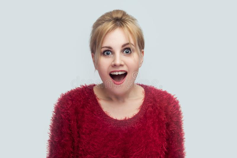 Portrait of amazed beautiful young blond woman in red blouse standing and looking at camera with surprised face and happiness news royalty free stock photos