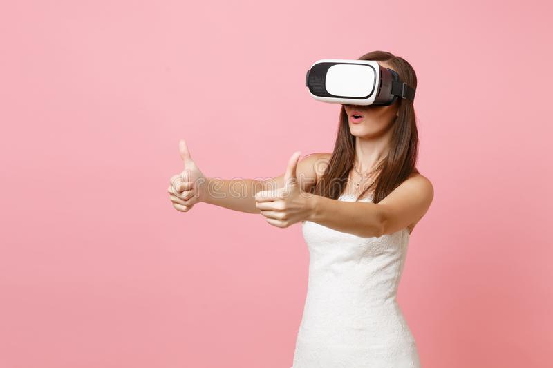 Portrait of amazed bride woman in white wedding dress, headset of virtual reality showing thumbs up isolated on pastel. Pink background. Organization of wedding royalty free stock photos