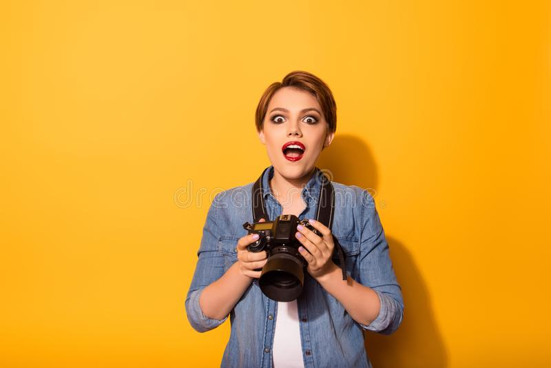 Portrait of amazed female photogrepher is casual clothes on the stock photography