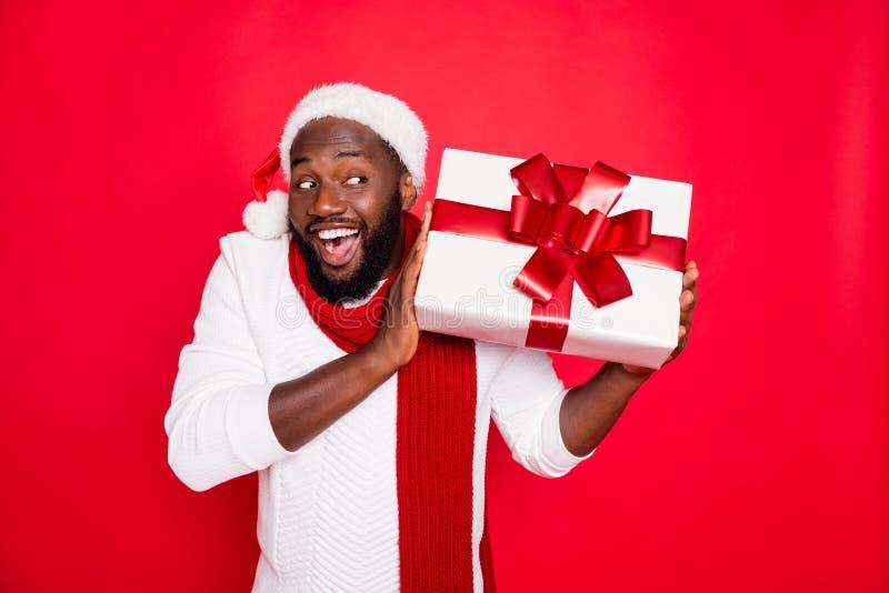 Portrait of amazed funky dark skin man wear santa claus headwear hold big package receive on x-mas time celebration. Portrait of amazed funky dark skin man wear stock image