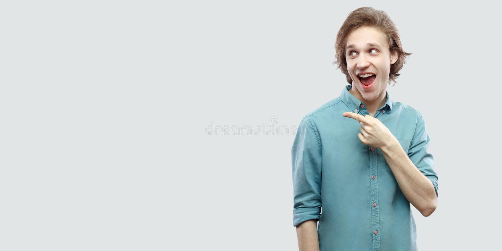 Portrait of amazed handsome long haired blonde young man in blue casual shirt standing and pointing at side copyspace with stock photography