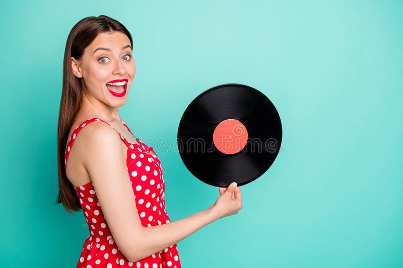 Portrait of amazed lady holding vinyl record screaming wow omg wearing dotted skirt dress isolated over teal turquoise. Portrait of amazed lady holding vinyl stock images