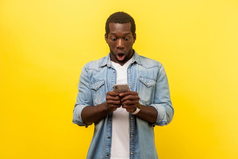 Portrait of amazed man using cellphone, typing text message or dialing number. isolated on yellow background royalty free stock photos