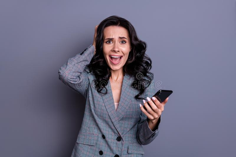 Portrait of amazed person with curly hairstyle touching her head yelling omg wearing jacket blazer isolated over grey. Portrait of amazed, person with curly royalty free stock photography