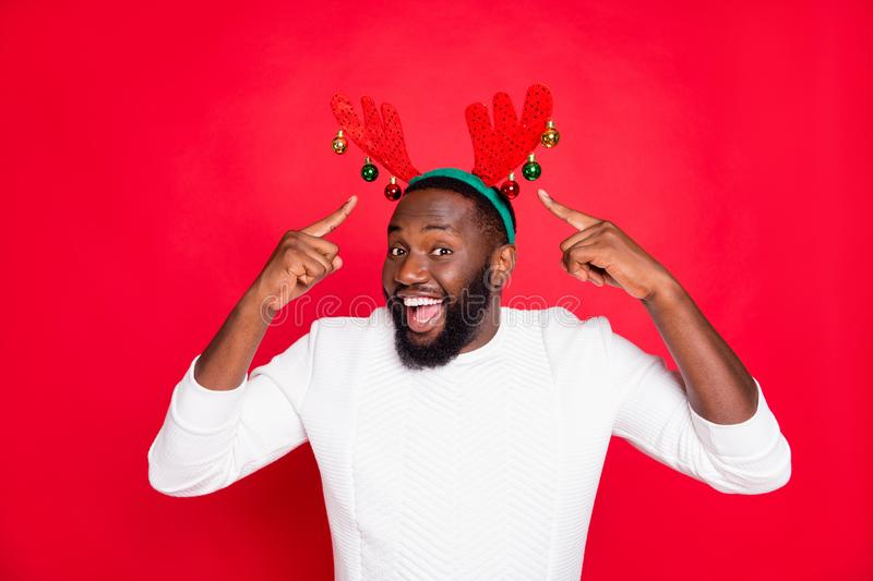Portrait of amazed surprised brown hair crazy black skin man point at rudolf deer horns enjoy his accessory for. Christmas eve party, celebration wear white royalty free stock images