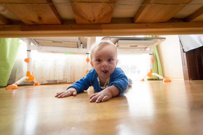 Funny portrait of amazed toddler boy lying on floor and looking under the bed stock photos