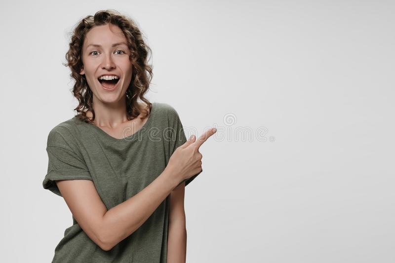 Portrait of amazed woman with opens eyes and mouth widely stupefied expression. Points aside with index finger, shows free copy space for your advertising stock photography