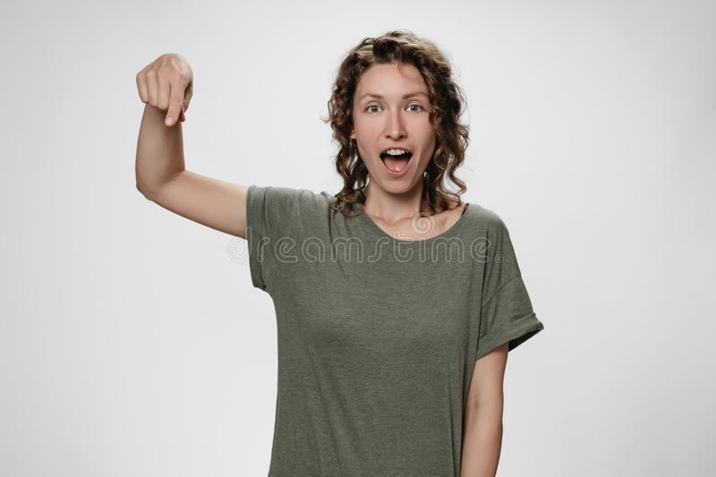 Portrait of amazed woman with opens eyes and mouth widely stupefied expression. Points down with index finger, shows free space for your advertising content royalty free stock photography