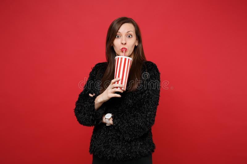 Portrait of amazed young woman in black fur sweater drinking cola or soda from plastic cup isolated on bright red royalty free stock image
