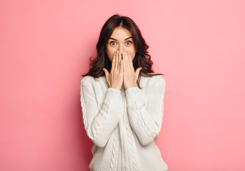 Portrait of amazed young woman over pink background royalty free stock photo