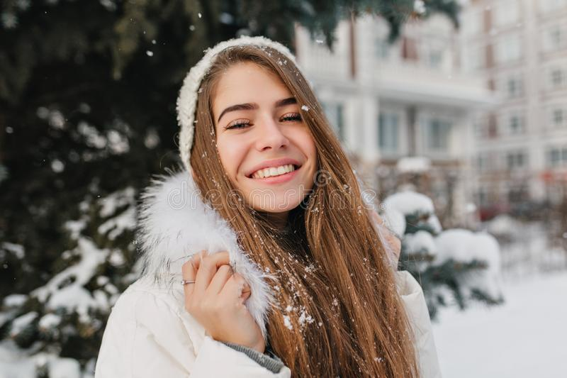 Portrait amazing joyful girl with long brunette hair in snow enjoying winter time on street. Brightful emotions, great stock photo