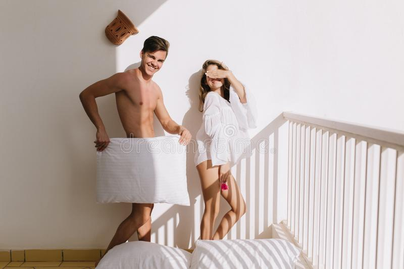Portrait of amazing slim girl and funny boy cover himself with white pillow and laughing. Handsome man with tanned skin royalty free stock photography