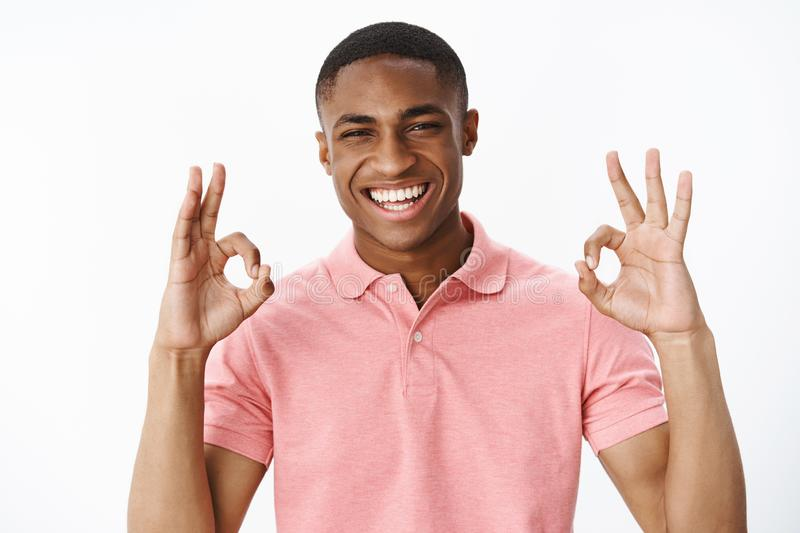 Portrait of ambitious good-looking african american young positive guy showing okay gesture with both hands and smiling stock image