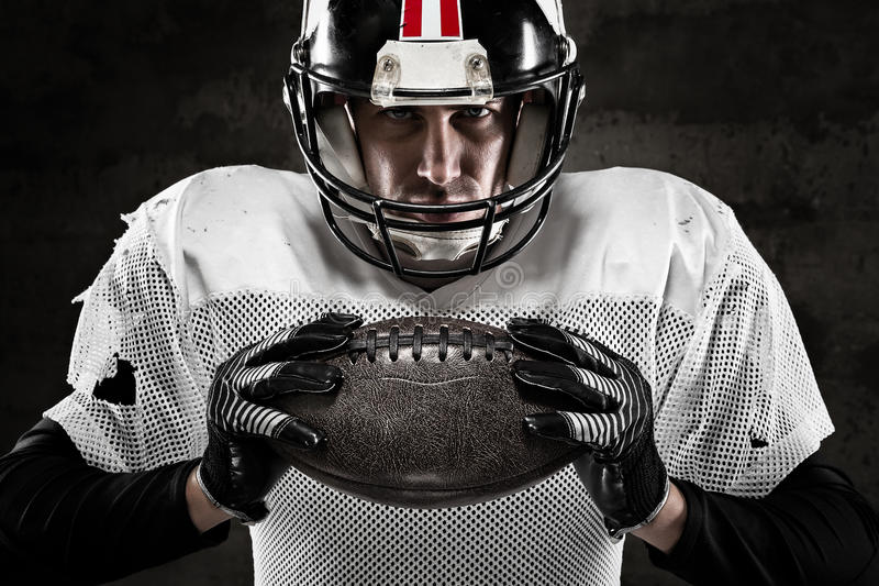 Portrait of american football player holding a ball royalty free stock image
