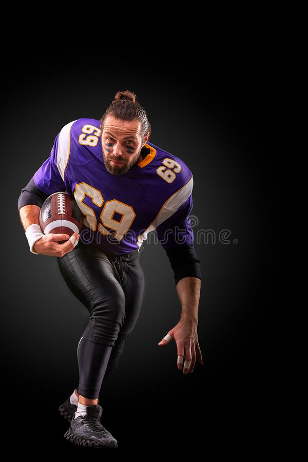 Portrait of American football player throwing ball over black background stock image