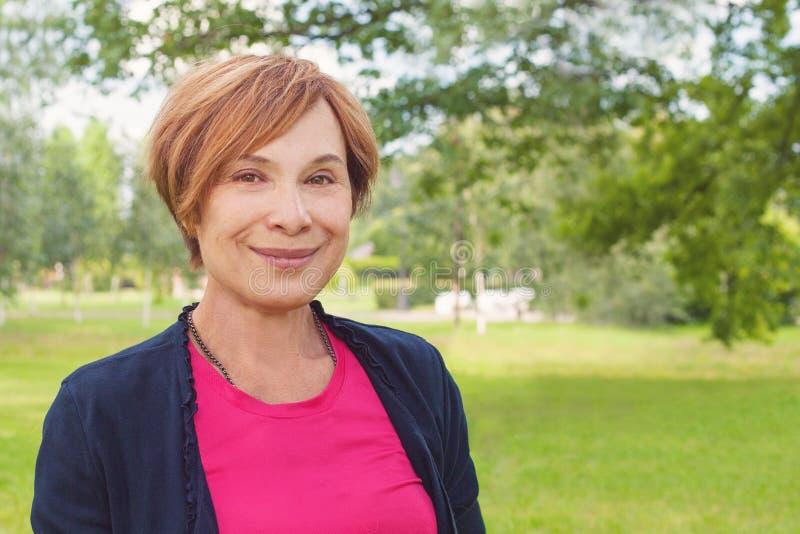 Portrait amical de plan rapproché de femme plus âgée Femme agée élégante heureuse en bonne santé avec le sourire court rouge de c images libres de droits
