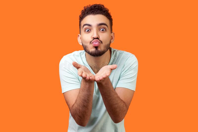 Portrait of amorous handsome brunette man holding palms up while sending air kiss. isolated on orange background. Portrait of amorous handsome brunette man with royalty free stock photography