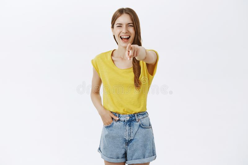 Portrait of amused cruel stylish popular girl in yellow t-shirt pulling index finger at camera and laughing out loud stock photography