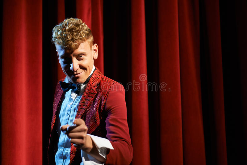 Portrait of anchorman at show against red curtain stock photography