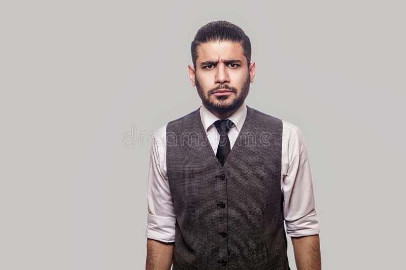Portrait of angry bossy handsome bearded brunette man in white shirt and waistcoat standing looking and frowning at camera with royalty free stock photos