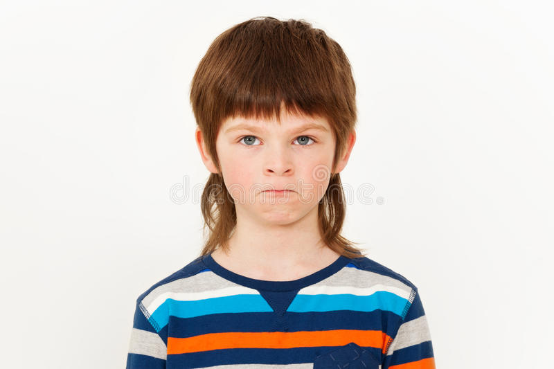Portrait of angry boy with his lips pursed. Portrait of angry seven years old boy with pursed lips, standing against white background royalty free stock photos