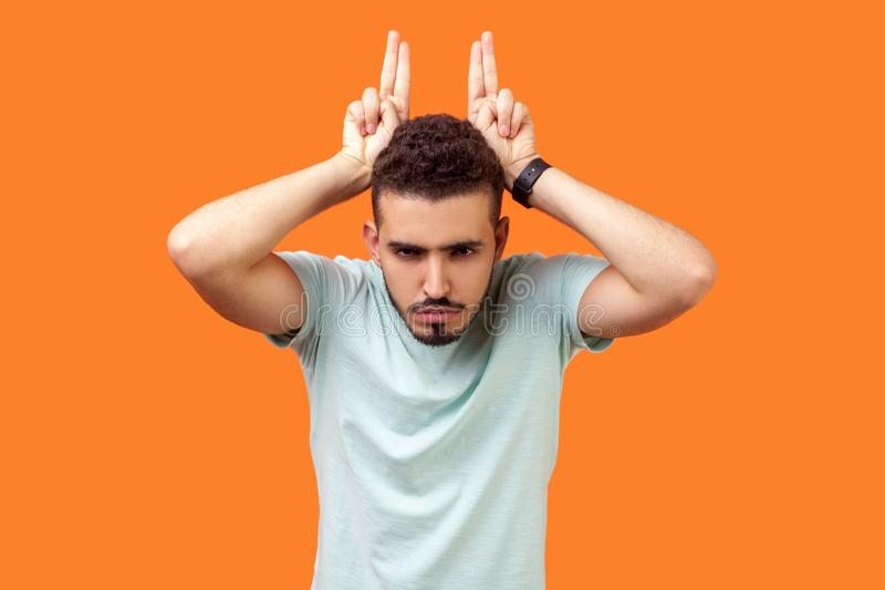 Portrait of angry bully brunette man showing bull horn gesture. indoor studio shot isolated on orange background stock photo