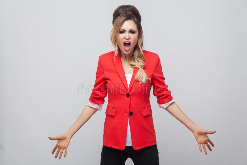 Portrait of angry business lady with hairstyle and makeup in red fancy blazer, standing raised arms, looking at camera and. Screaming. indoor studio shot stock photo
