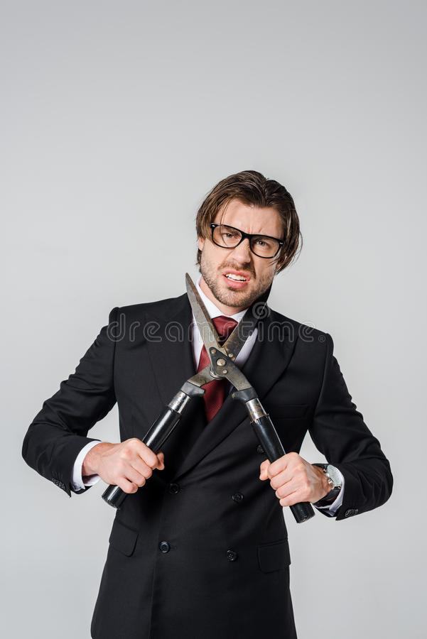 portrait of angry businessman in black suit with clipper in hands stock photography