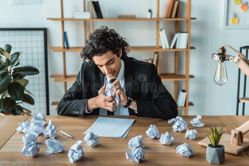 portrait of angry businessman crumpling papers at workplace stock photo