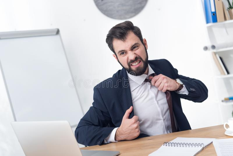 portrait of angry businessman looking at laptop screen at workplace royalty free stock image
