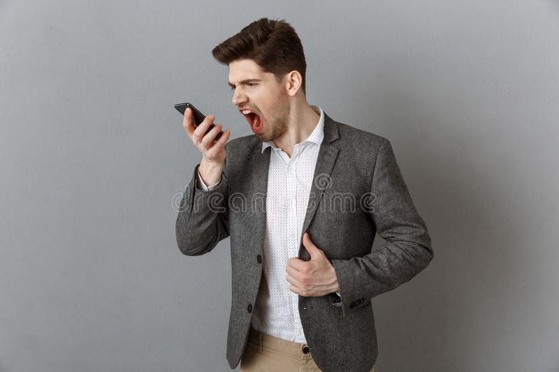 portrait of angry businessman screaming while talking on smartphone against grey stock image