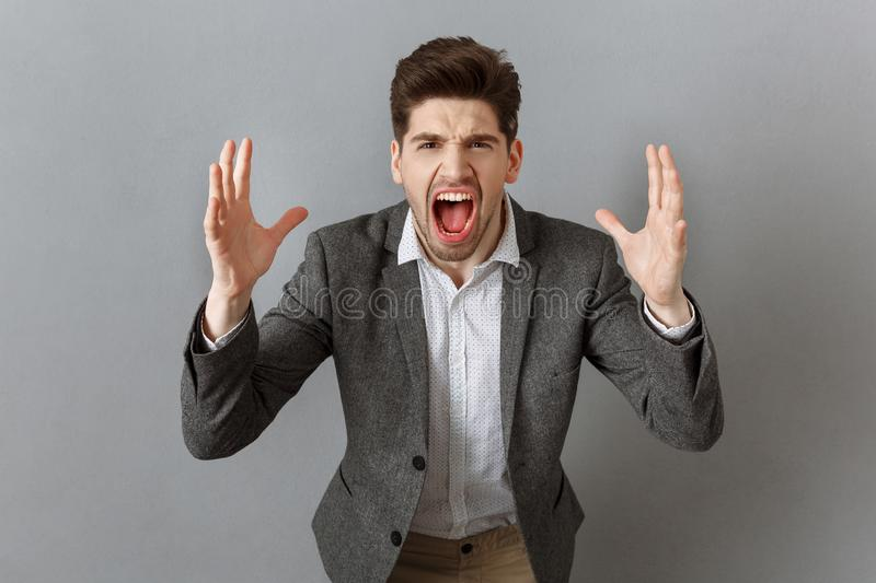 portrait of angry businessman in suit gesturing and looking at camera against grey royalty free stock photography