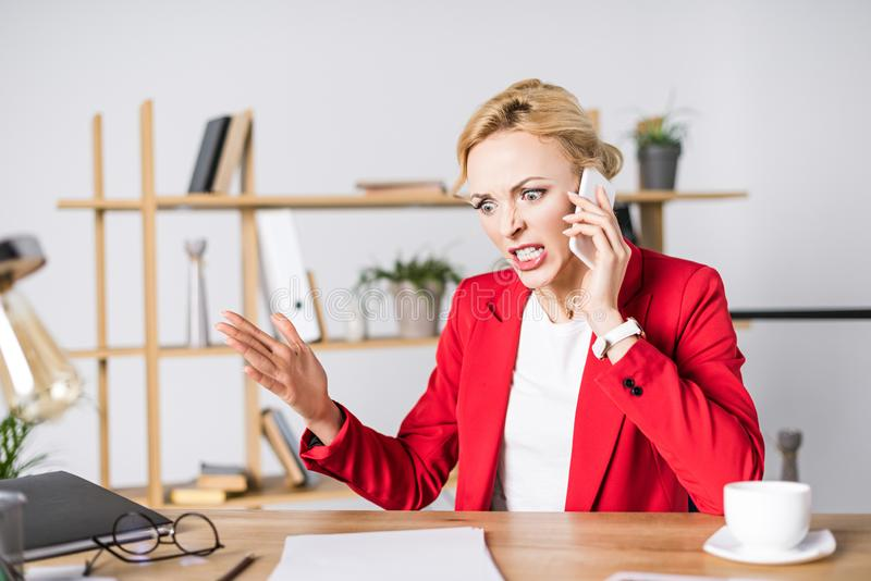 portrait of angry businesswoman talking on smartphone at workplace stock photography