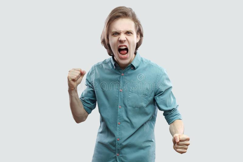 Portrait of angry crazy handsome long haired blonde young man in blue casual shirt standing, looking at camera, screaming and stock photo