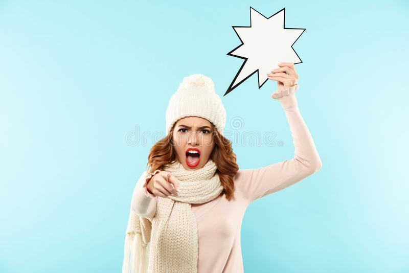 Portrait of an angry furious girl dressed in winter clothes. Holding paper speech bubble and pointing finger at camera isolated over blue background stock photography