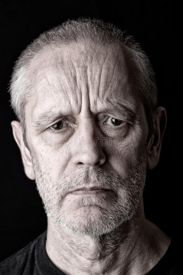Portrait of an Angry and Furious Man. Portrait of a serious and angry man with a penetrating gaze and fury in the eyes stock images