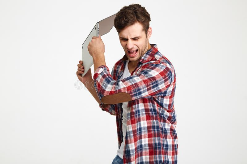 Portrait of an angry furious man throwing his laptop computer. Isolated over white background stock image