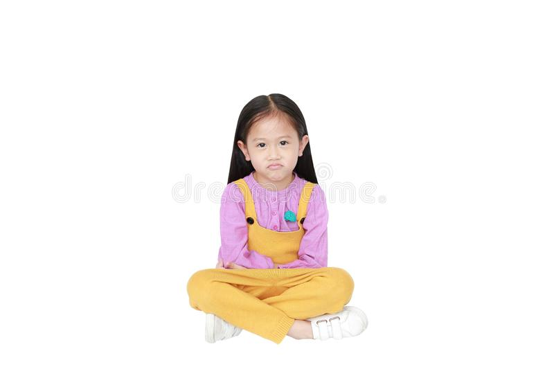 Portrait of angry little Asian child girl in pink-yellow pink-yellow dungarees sitting isolated on white background with copy royalty free stock images