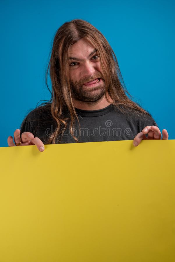 Portrait of angry male displaying a grimace while holding a yellow banner for advertise. Copy space for message job idea royalty free stock image