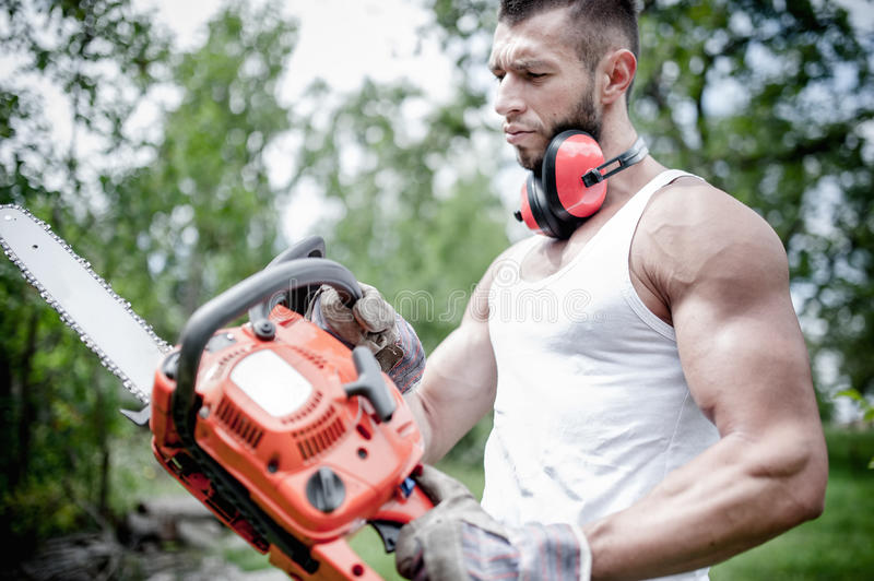 Portrait of angry muscular male lumberjack, woodworker. With chainsaw in hand, posing royalty free stock photos