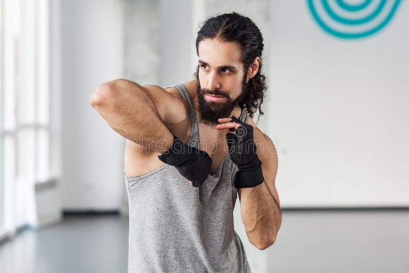 Portrait of angry muscular young adult man with curly hair standing and preparing to fight with elbow in black gloves, showing stock photography