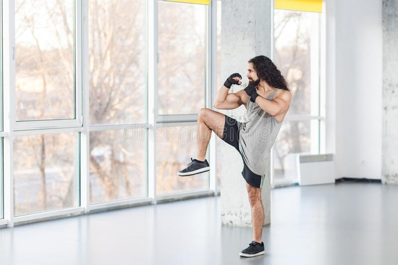 Portrait of angry muscular young adult man with curly long hair standing and preparing to fight with fist in black gloves and knee royalty free stock photos