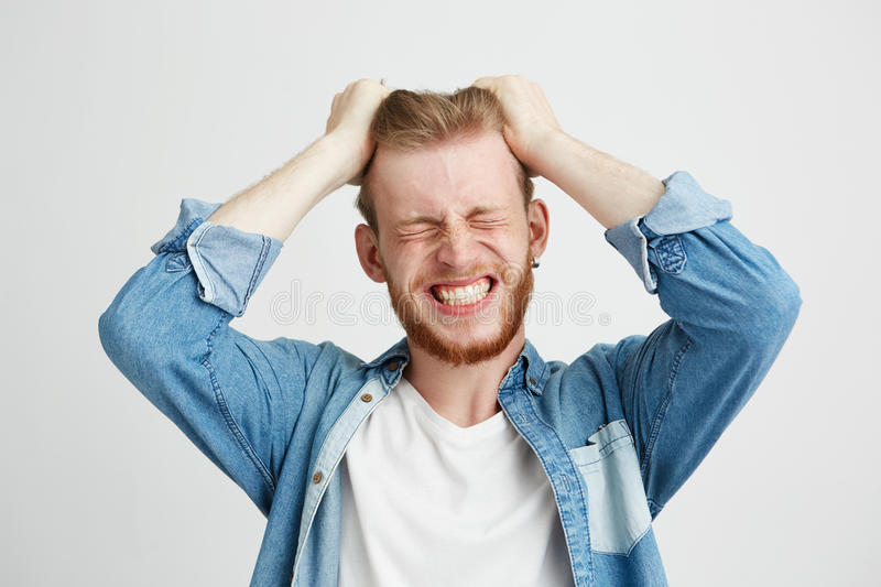 Portrait of angry rage young man touching his hair clenched teeth over wite background. Closed eyes. Copy space stock photo