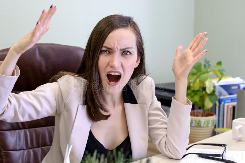 Portrait of angry, screaming young business woman in a leather chair behind the office Desk royalty free stock photography