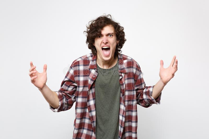 Portrait of angry screaming young man in casual clothes looking camera, spreading hands isolated on white wall royalty free stock image