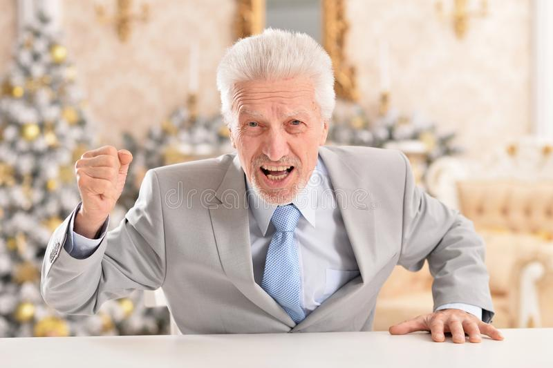 Portrait of angry senior businessman at table. Portrait of angry senior businessman sitting at table stock photography
