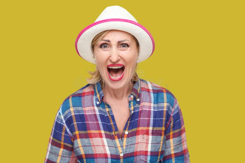 Portrait of angry or shocked modern stylish mature woman in casual style with white hat standing and looking at camera and royalty free stock photography
